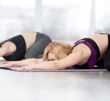 """Fitness, stretching practice, group of two attractive fit mature women working out in sports club, """"warming up"""", doing Frog Yin Yoga Pose, Mandukasana posture in class, full length"""